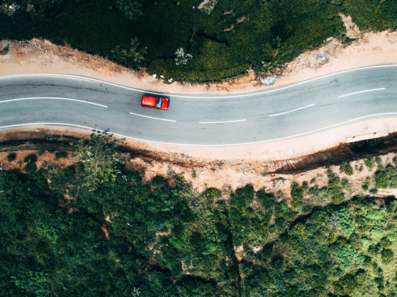 Aerial view on  red car on the road near green tea plantation in mountains in Sri Lanka